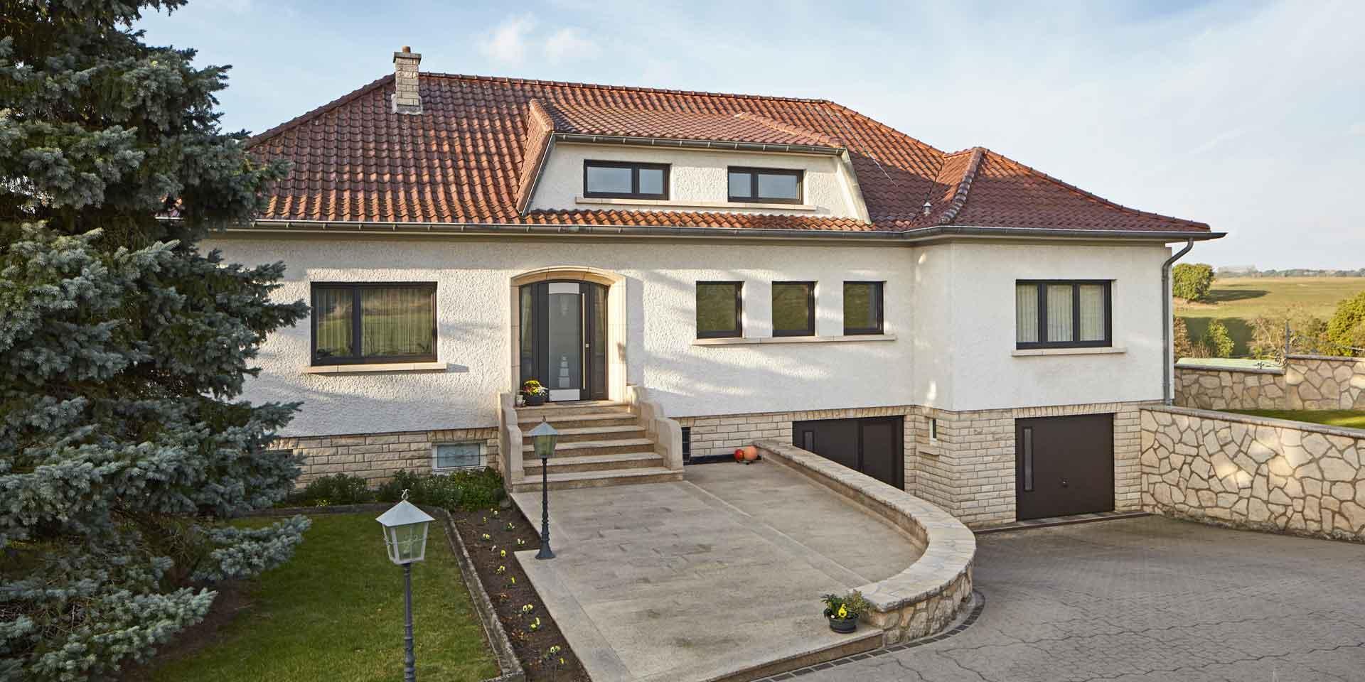 Weißes Einfamilienhaus in Emerange mit einer grauen Coplaning Alu Haustür mit Seitenteilen aus Glas und grauen Coplaning Alu Fenster.
