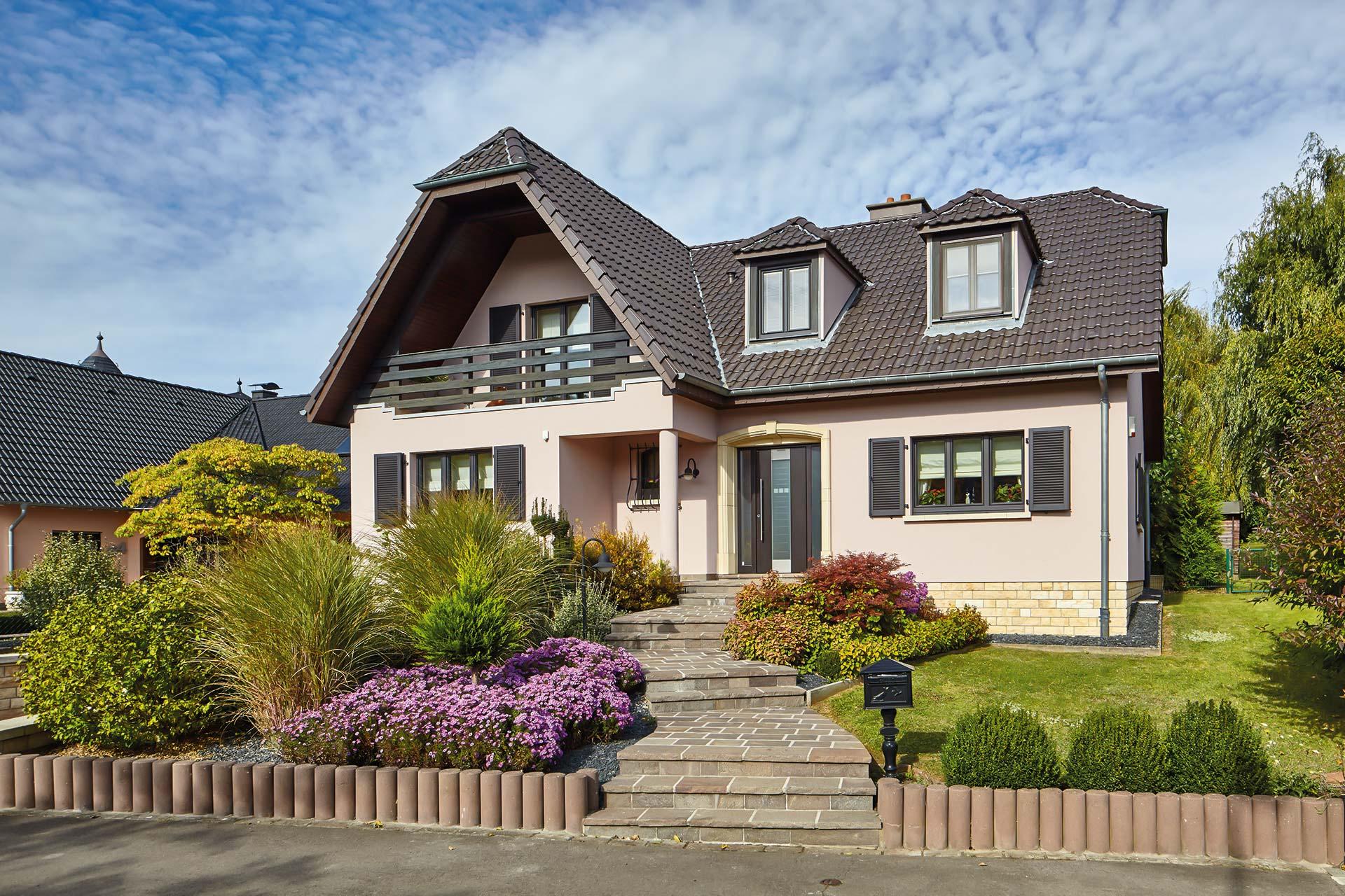 Leicht pinkes Einfamilienhaus mit einer grauen Coplaning Alu Haustür und grauen Coplaning Holz- Alu Fenster mit passenden Klappläden.