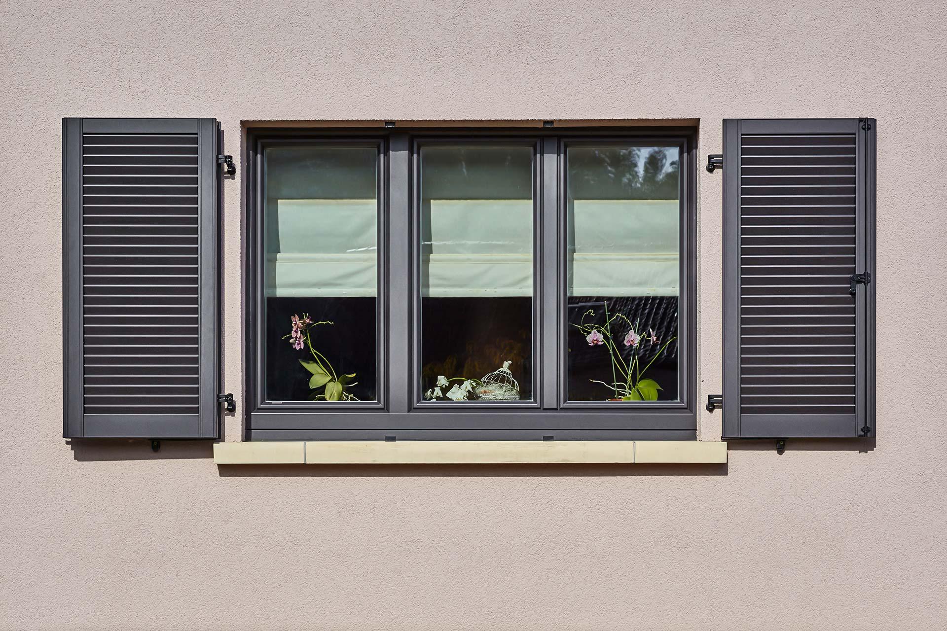Nahaufnahme eines grauen Coplaning Holz- Alu Fenster des leicht pinken Einfamilienhauses.