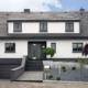 Modernes grau-weißes Einfamilienhaus mit grauer moderner Coplaning Haustür und grauen Coplaning Fenster.