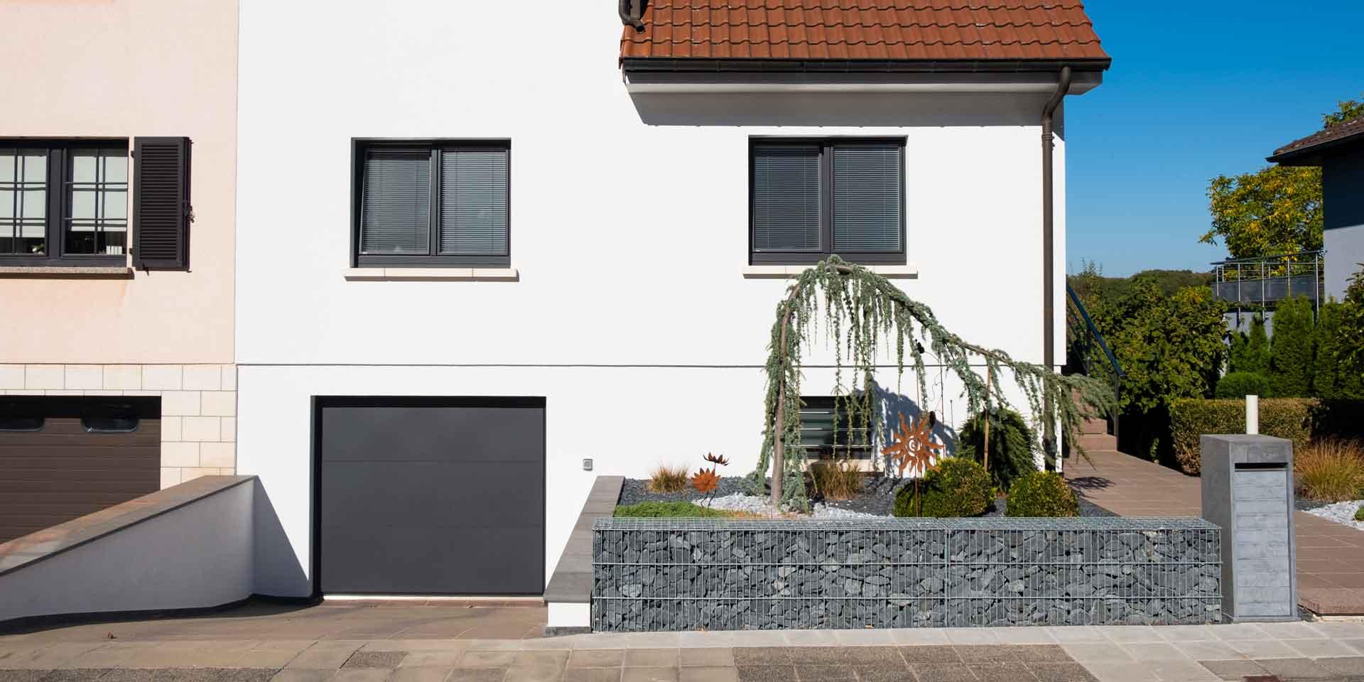 Weißes Einfamilienhaus mit grauen Coplaning Holz-Alu Fenster.