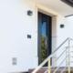 Nahaufnahme des Eingangsbereichs eines weißen Einfamilienhauses mit Blick auf eine neue moderne graue Coplaning Haustür mit großem Lichtausschnitt.