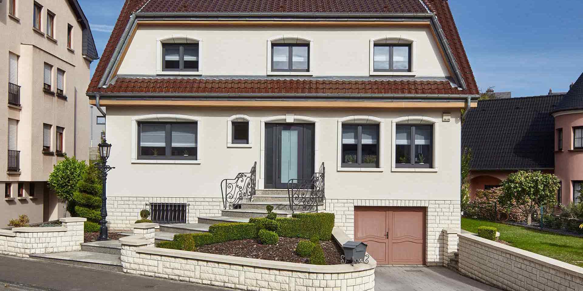 Weißes Einfamilienhaus mit grauer moderner Coplaning Haustür und grauen Holz-Alu-FensternFenster.