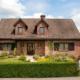 Einfamilienhaus mit Klinkerfassade mit einer braunen klassischen Coplaning Haustür und braunen Coplaning PVC Alu Fenster.