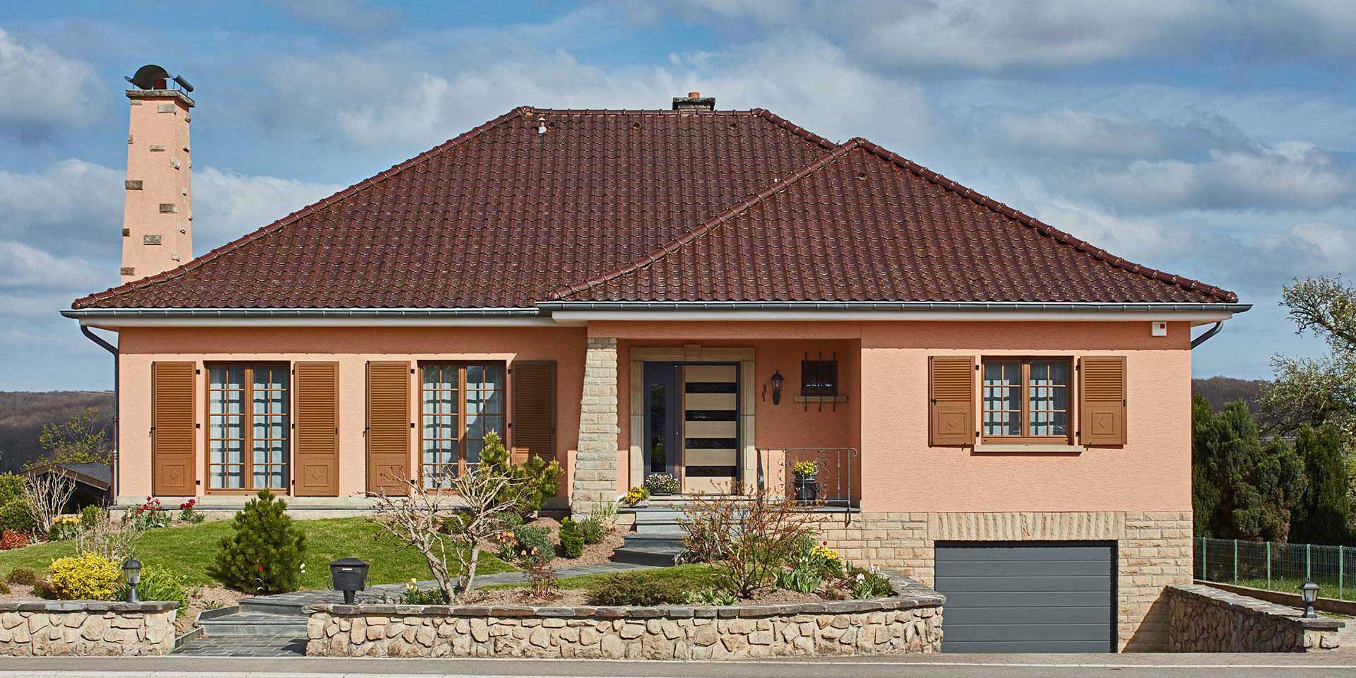 Modernisierung eines orangen Einfamilienhaus mit neuer moderner grau-keramik Coplaning Haustür und braunen modernen Coplaning Fenster mit Klappläden.