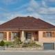 Modernisierung eines orangen Einfamilienhaus mit neuer moderner grau-keramik Coplaning Haustür und braunen modernen Fenster mit Klappläden.