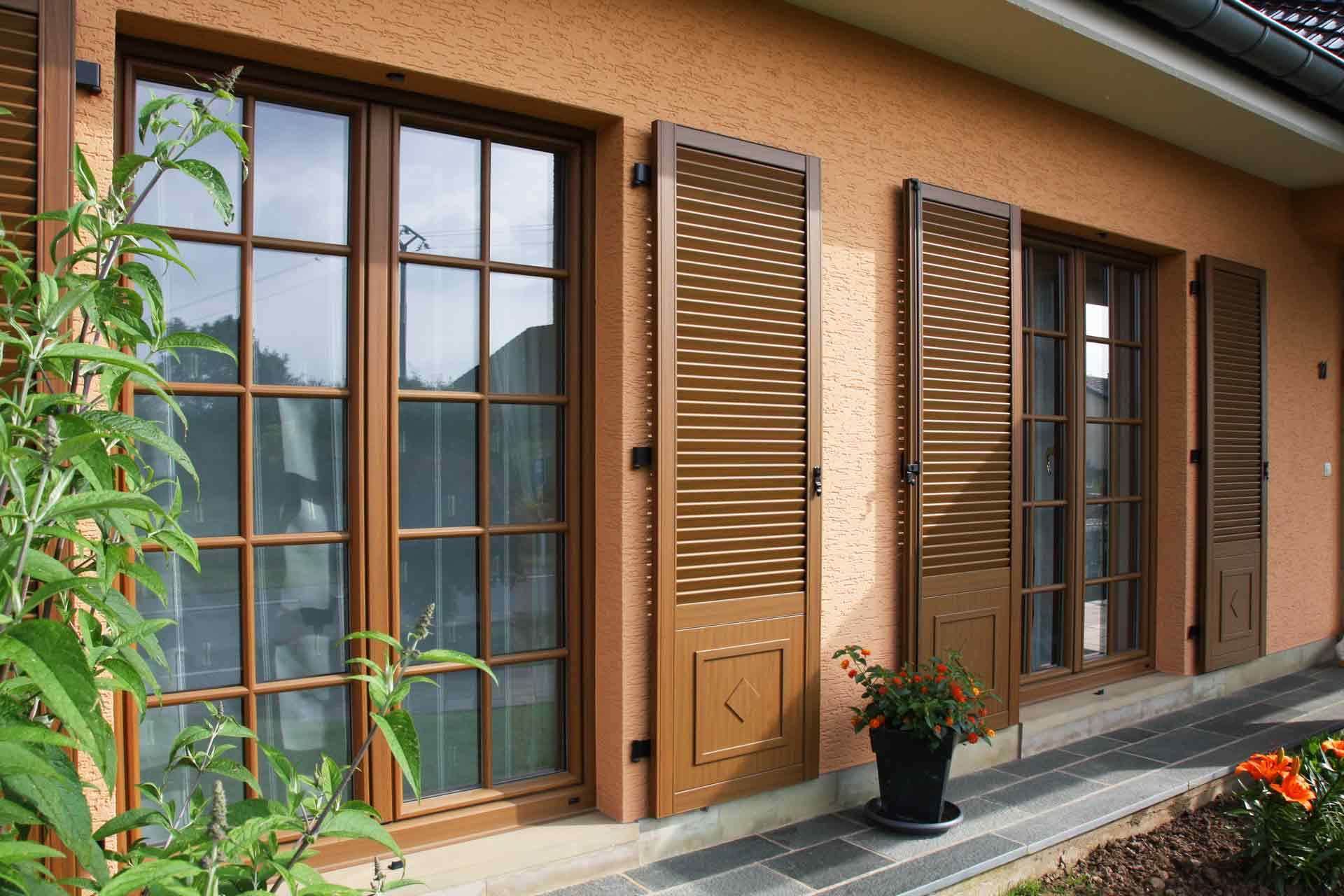 Nahaufnahme von zwei Coplaning Fenster mit Klappläden von dem orangen Einfamilienhaus.