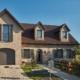 Einfamilienhaus mit Steinfassade mit neuer grauen runden Coplaning Alu Haustür mit grauen Coplaning Holz- Alu Fenster und einem grauen Garagentor.