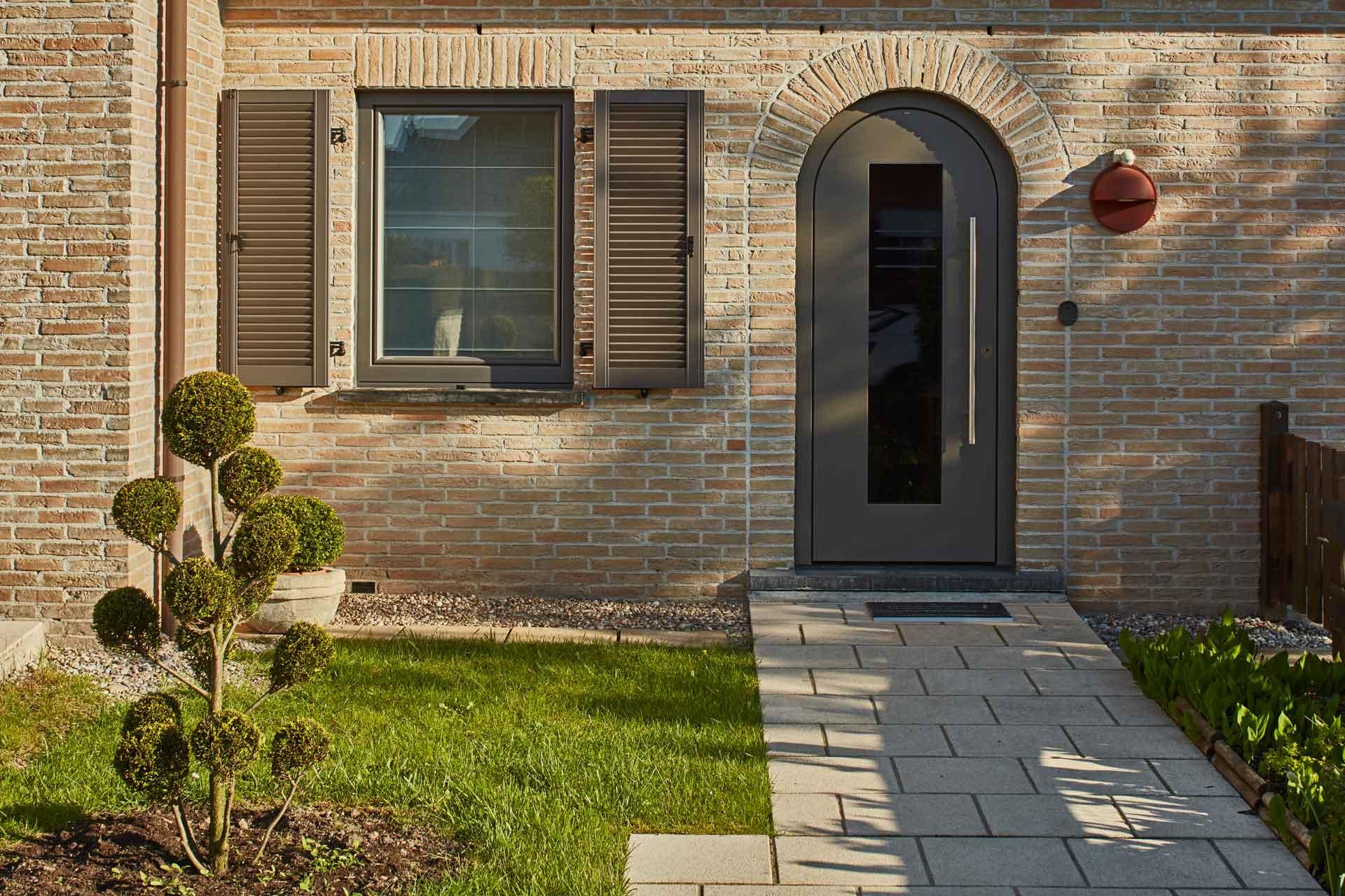 Nahaufnahme des Eingangsbereich eines Einfamilienhauses mit Steinfassade mit einer neuen runden Coplaning Haustür und links davon ein graues Coplaning Alu Fenster.