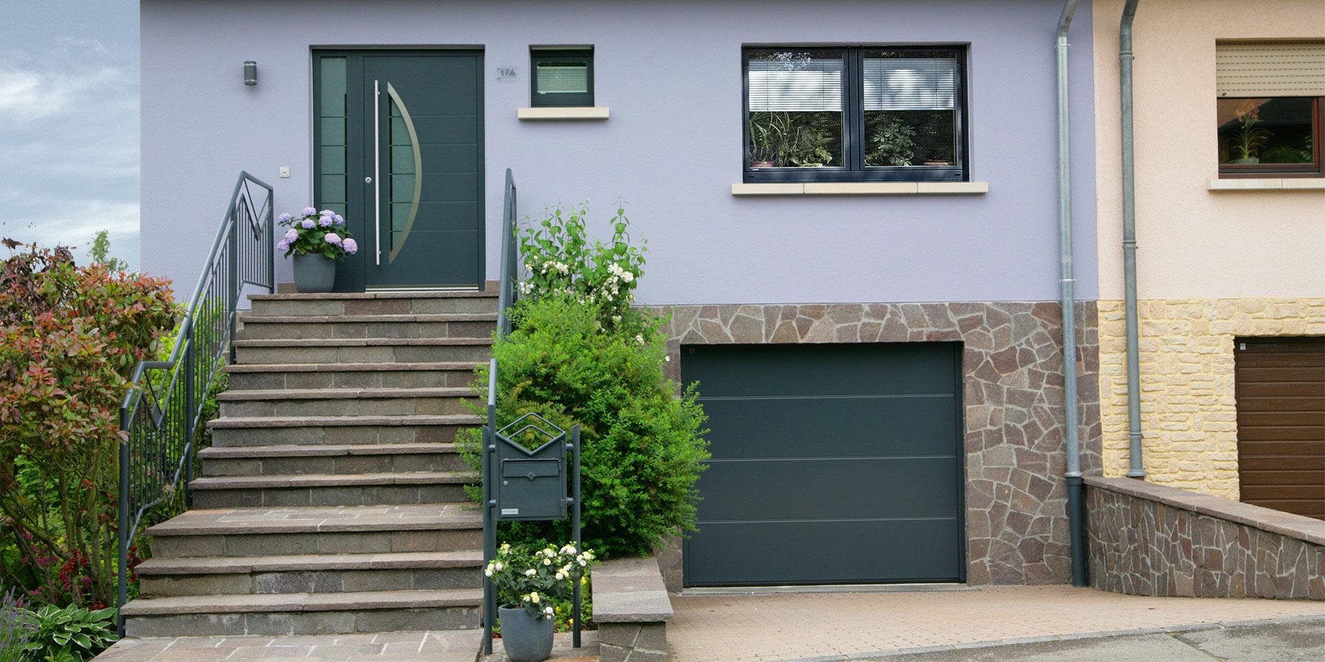 Lila Einfamilienhaus mit einer grau lackierten Coplaning Haustür, grauen Coplaning Fenster und einem grauen Coplaning Garagentor.