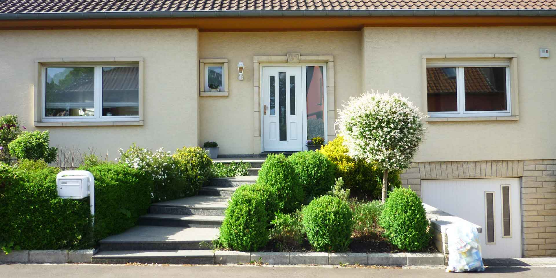 Gelbliches Einfamilienhaus mit einer weißen Coplaning Lack Haustür mit Glas und einem weißen Coplaning Garagentor mit Glausausschnitten.