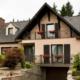 Leicht pinkes Einfamilienhaus mit einer braunen Coplaning Alu Lack Haustür, braunen Coplaning Alu Fenster mit braunen Alu Klappläden.