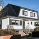 Weißes Einfamilienhaus mit grauen modernen Klappläden, einer grauen Coplaning Haustür und einer grauen Garage mit Lichtausschnitten.