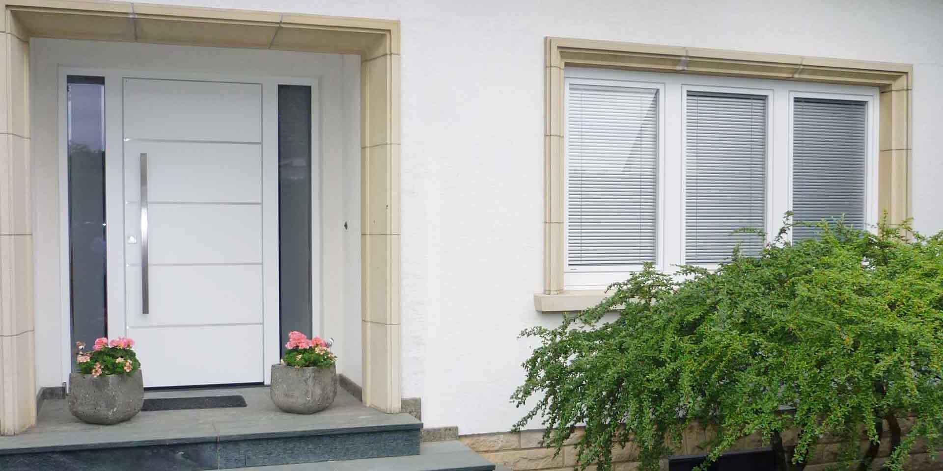 Nahaufnahme auf den Eingangsbereich des weißen Einfamilienhauses mit Blick auf die neue moderne weiße Coplaning Haustür und rechts davon drei weißen Kunststoff Coplaning Fenster.