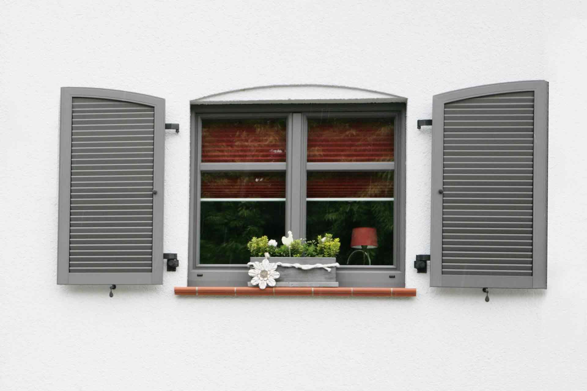 Nahaufnahme eines weiß- grauen Einfamilienhauses mit Blick auf ein graues Coplaning Alu Fenster mit grauen Klappläden.