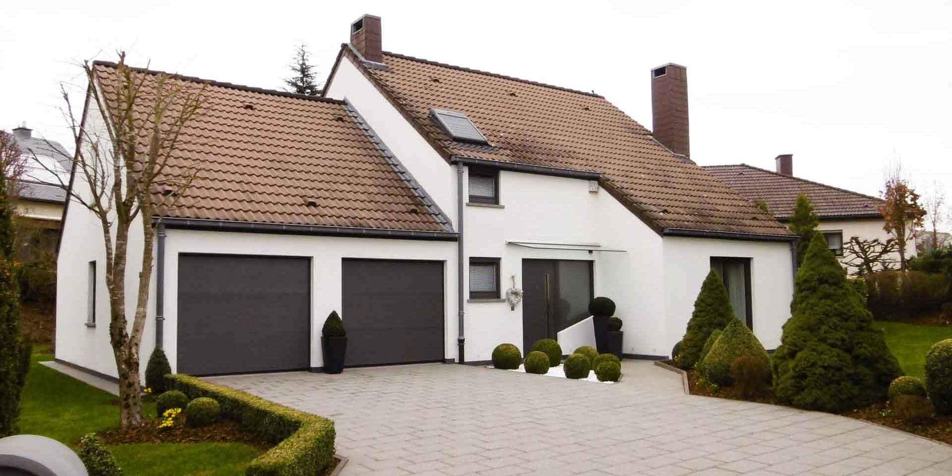 Weißes Einfamilienhaus mit einer grauen Coplaning Alu Haustür, grauen Coplaning Jalousienfenster und einem grauen Coplaning Garagentor.