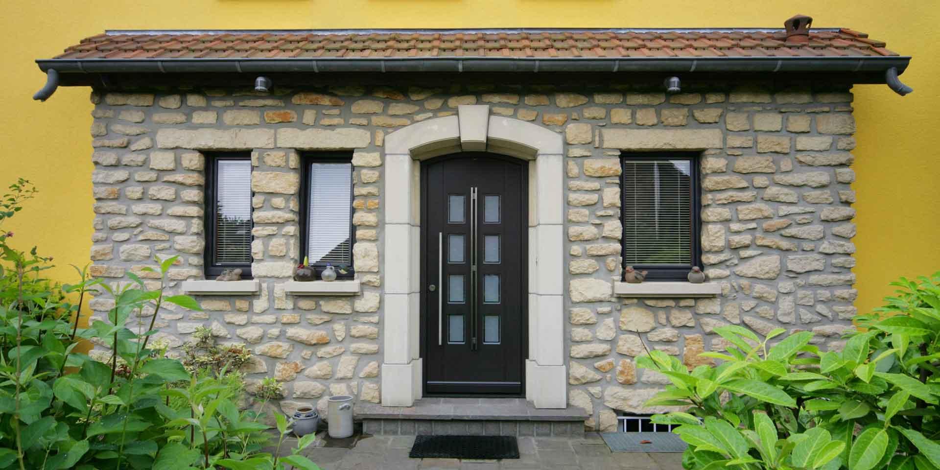Nahaufnahme des Eingangsbereis eines gelben Einfamilienhauses mit einer rustikal braunen Coplaning Haustür und mit braunen Coplaning Holz Jalousiefenstern.