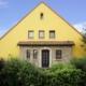Gelbes Einfamilienhaus mit brauner Coplaning Haustür und braunen Coplaning Holz Jalousiefenster.