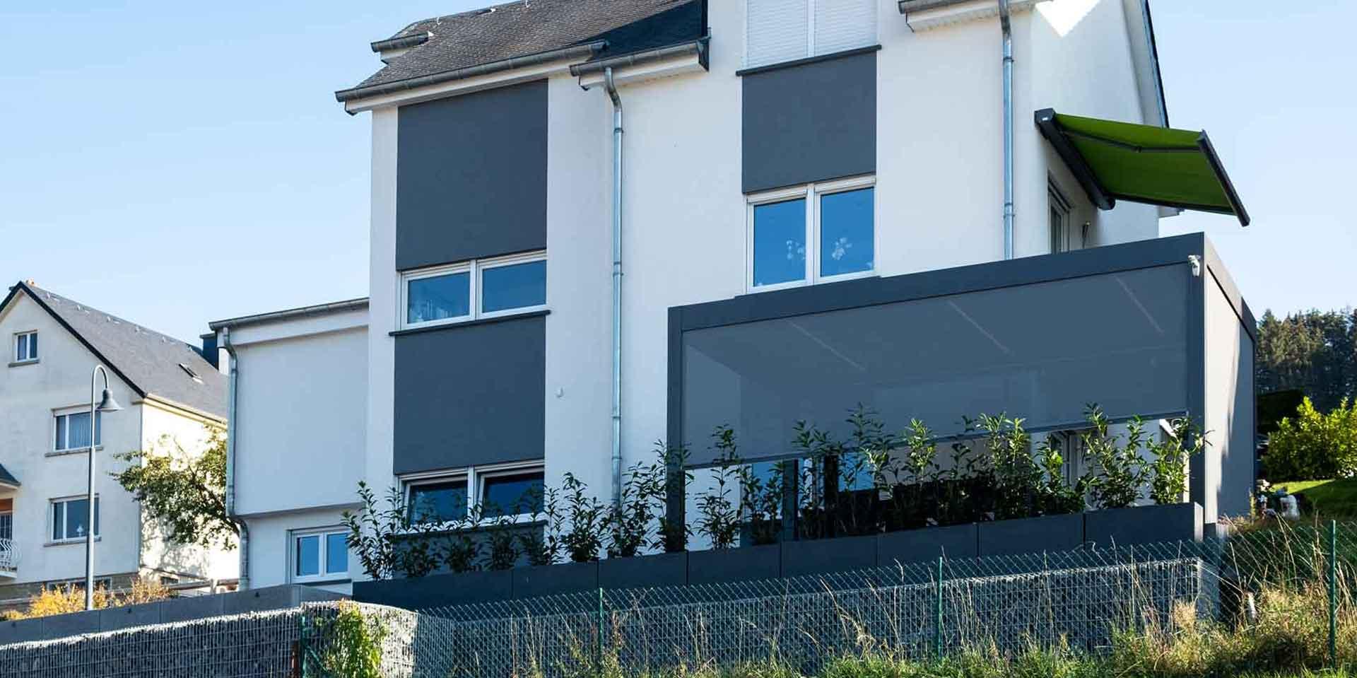 Weißes Einfamilienhaus mit Blick auf eine graue Alu Coplaning Veranda Terassenüberdachung mit Lamellendach und kippbarem Lamellendach mit LED-Licht.