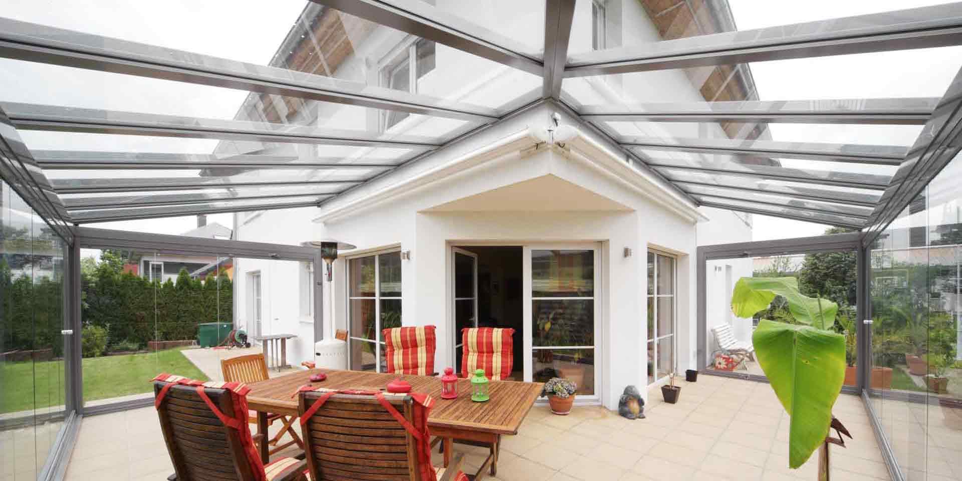 Weißes Einfamilienhaus mit Nahaufnahme der Rückseite des Hauses mit Blick auf eine Coplaning Veranda Glasschiebewand mit einer grauen Aluminium Glasüberdachung mit Terassenüberdachung um die Ecke.