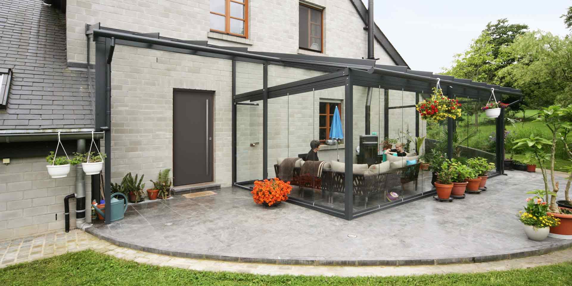 Graues Einfamilienhaus mit einer grauen Coplaning Aluminium Veranda Glasfaltwand mit Terassenüberdachung.