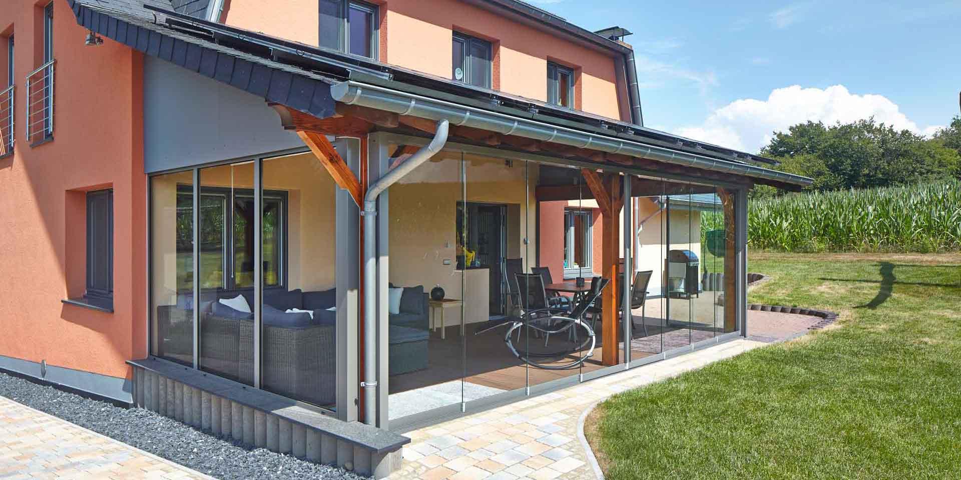Oranges Einfamilienhaus mit Nahaufnahme der Rückseite des Hauses mit Blick auf ein Coplaning Terassen Wintergarten mit einer grauen Coplaning Glasfaltwand ohne Rahmenprofile.