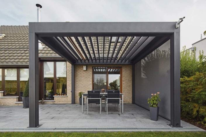 Einfamilienhaus mit Steinfassade mit einem grauen Coplaning Veranda Quadrato mit Terassenüberdachung und einem Lamellendach aus Aluminium mit Windschutz.