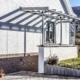 Weißes Einfamilienhaus mit einer Coplaning Veranda Überdachung aus Glas und Aluminium mit grauem Witterungsschutz.