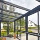 Nahaufnahme des inneren der grauen Coplaning Veranda Überdachung aus Aluminium und mit grauem Balkon mit Treppenbereich und Verglasung mit Schiebefenster.