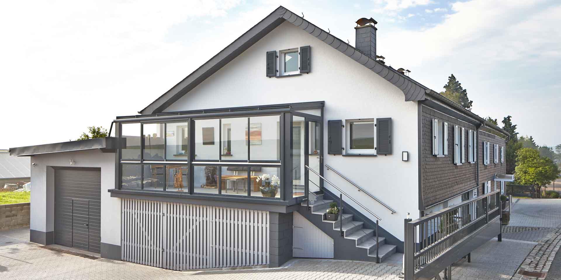 Weißes Einfamilienhaus mit einer Coplaning Veranda Überdachung aus Aluminium, grauem Balkon mit Treppenbereich und einer Verglasung mit Schiebefenster und integrierter Beleuchtung.