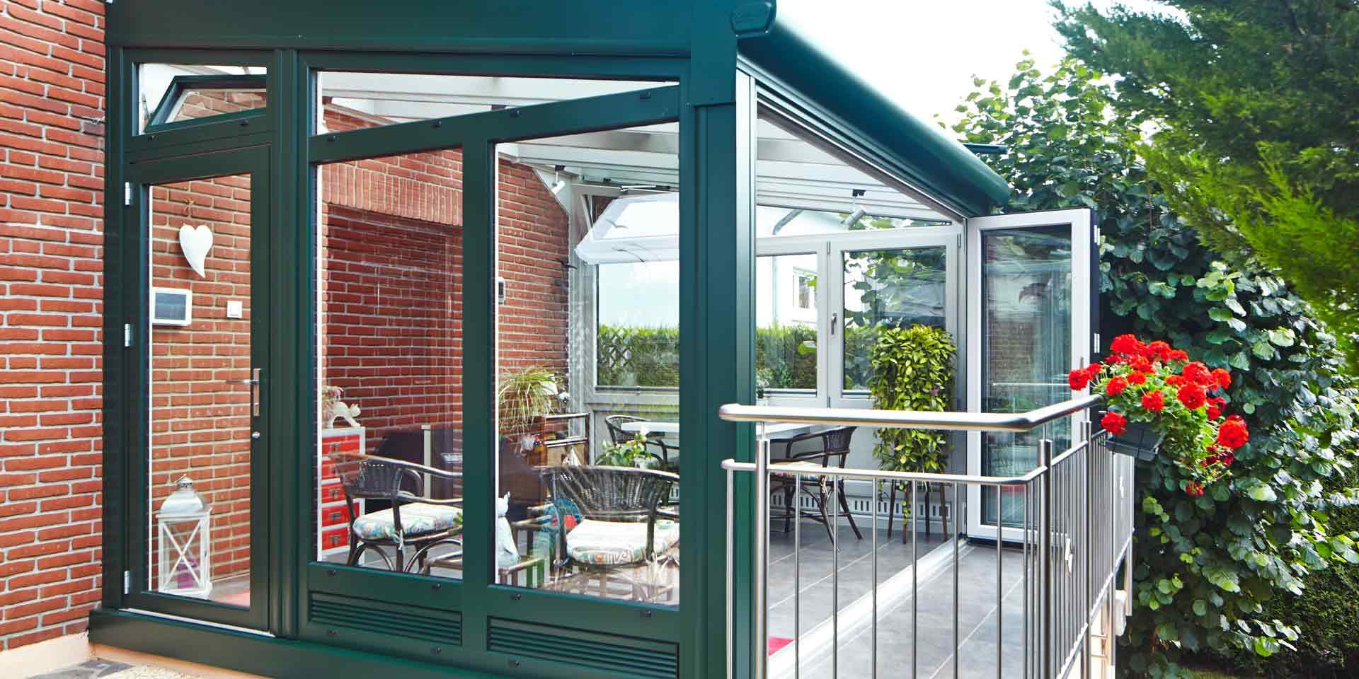 Einfamilienhaus mit Steinfassade mit Nahaufnahme der Rückseite mit Blick auf ein grüner Coplaning Alu Veranda Wintergarten mit weißer geöffneten Faltanlage und Kippfenster.