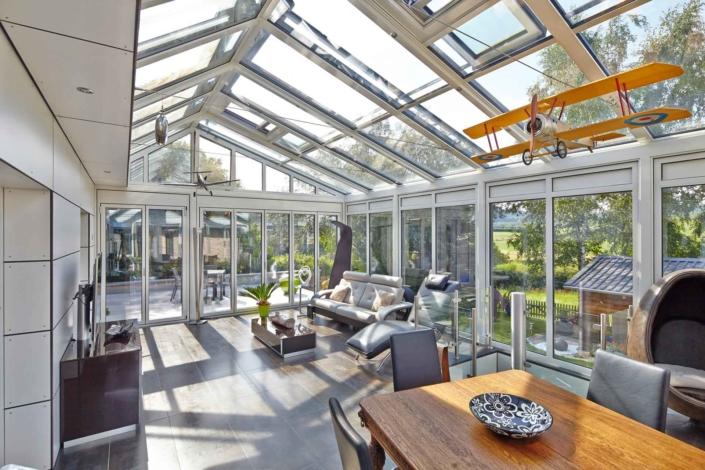 Einfamilienhaus mit Steinfassade mit Nahaufnahme des inneren Bereichs des Coplaning Veranda Wintergarten mit hellgrauer Aluminium Faltanlage mit Glasdach.