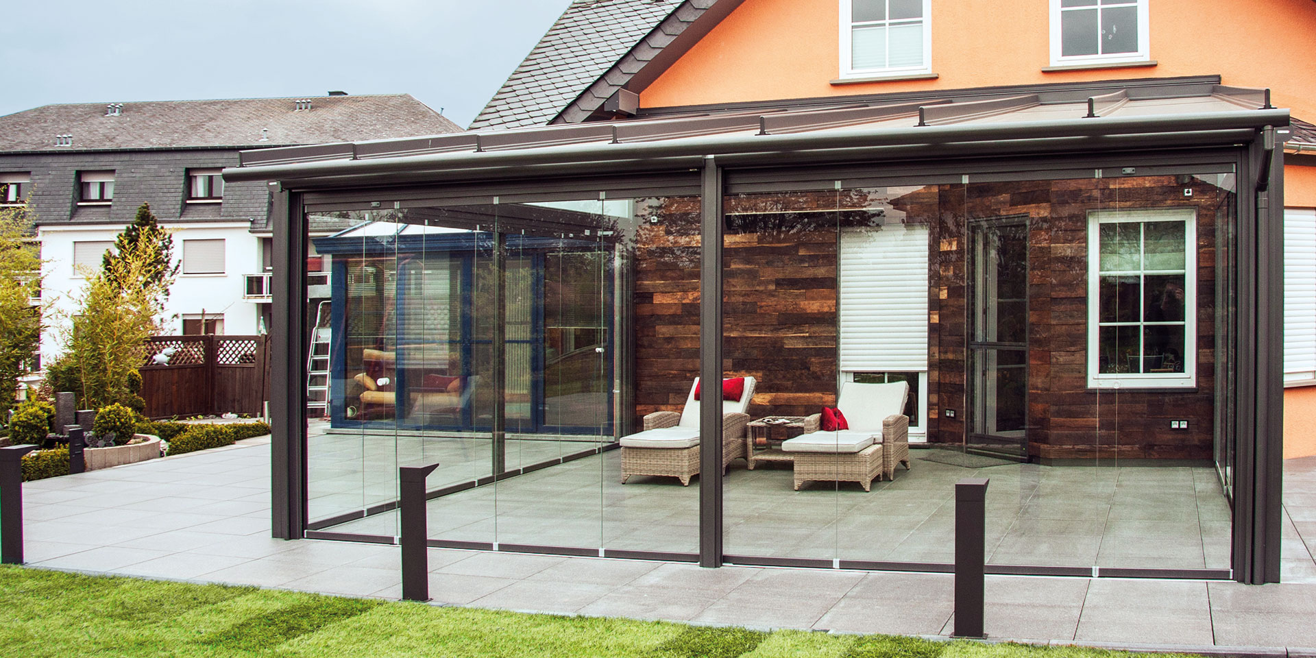 Oranges Einfamilienhaus mit einer Coplaning Veranda verglasten Terasse mit grauer Alu- Innenmarkise und integrierter Beleuchtung.