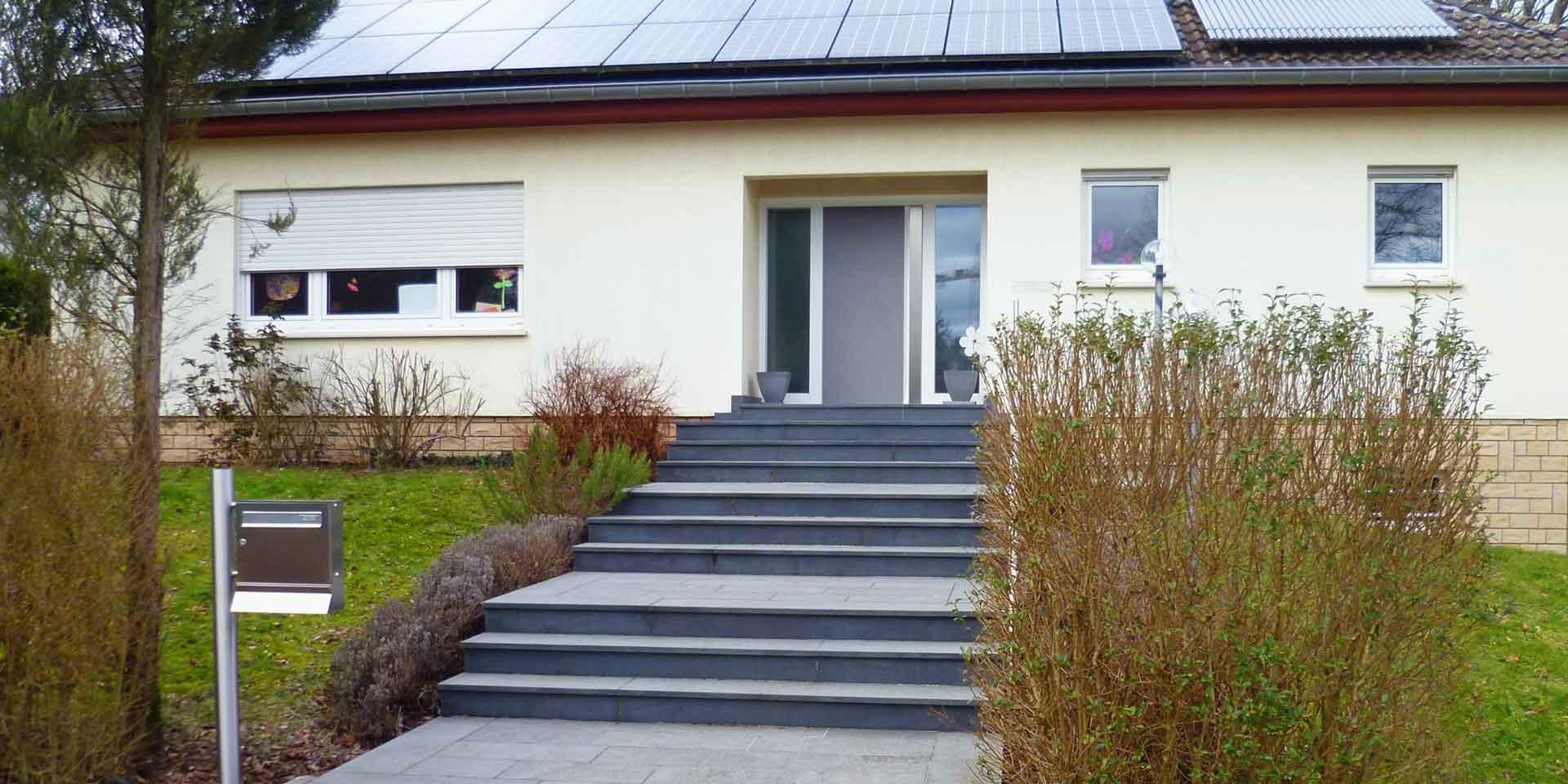 Gelbliches Einfamilienhaus mit moderner grauer Coplaning Haustür und weißen Coplaning Fenstern.