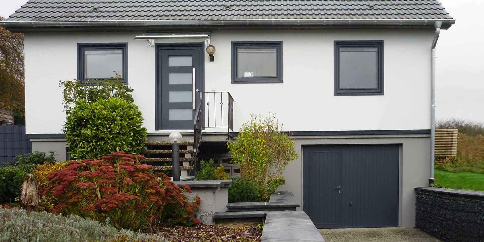 Weißes Einfamilienhaus mit moderner grauer Coplaning Haustür und grauen Coplaning Holz- Alu Fenster.