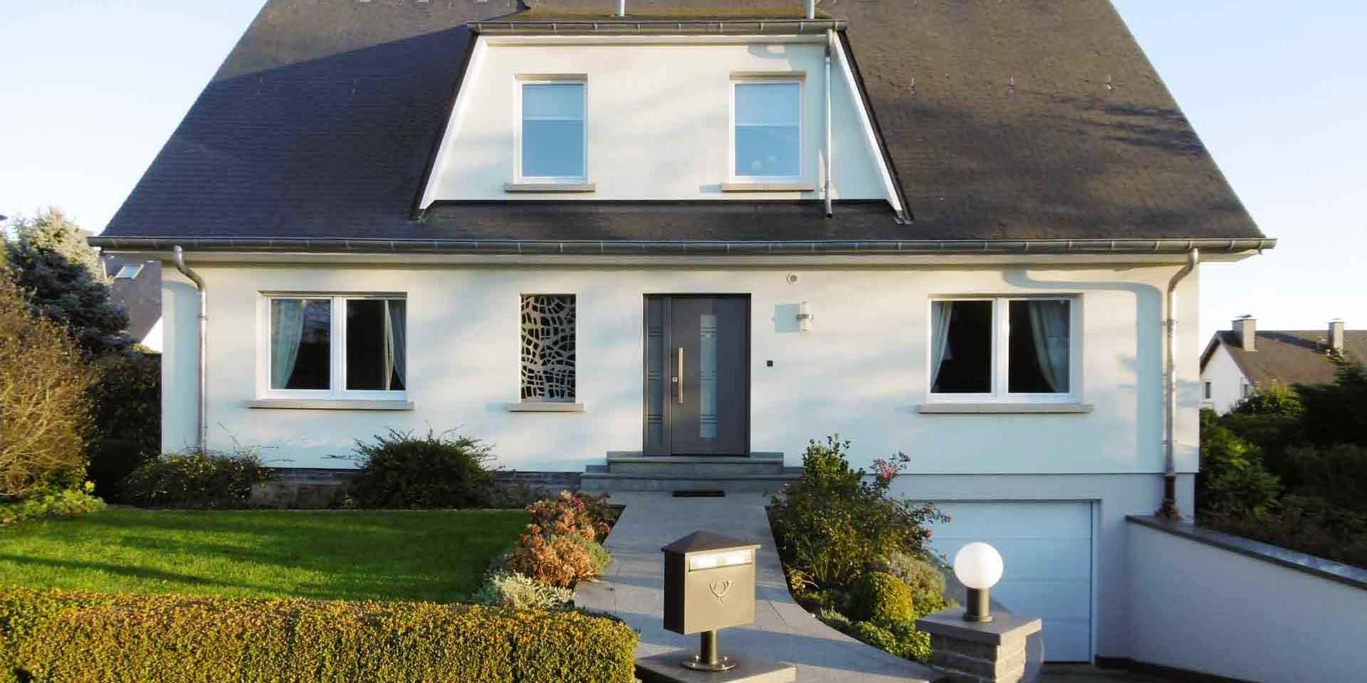 Weißes Einfamilienhaus mit einer grauen Coplaning Lack Haustür.