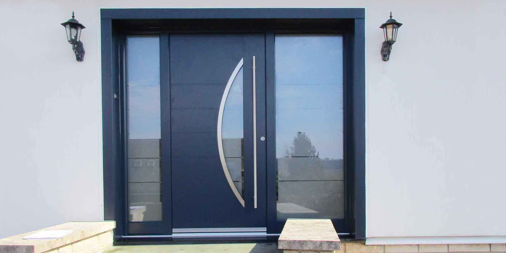 Nahaufnahme des Eingangsbereiches eines weißen Einfamilienhauses mit Blick auf eine graue Coplaning Aluminium Lack Haustür.