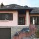 Vorderseite eines leicht pinken Einfamilienhauses mit brauner modernen Coplaning Haustür und braunen Fensterläden.
