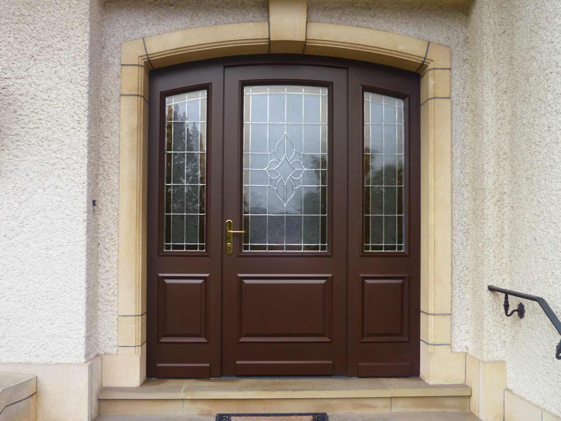 Nahaufnahme des Eingangsbereichs eines weißen Einfamilienhauses mit Blick auf die neue braune Coplaning Haustür.