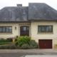 Weißes Einfamilienhaus mit neuer Bleiglas verglasten braunen Coplaning Holz Haustür.