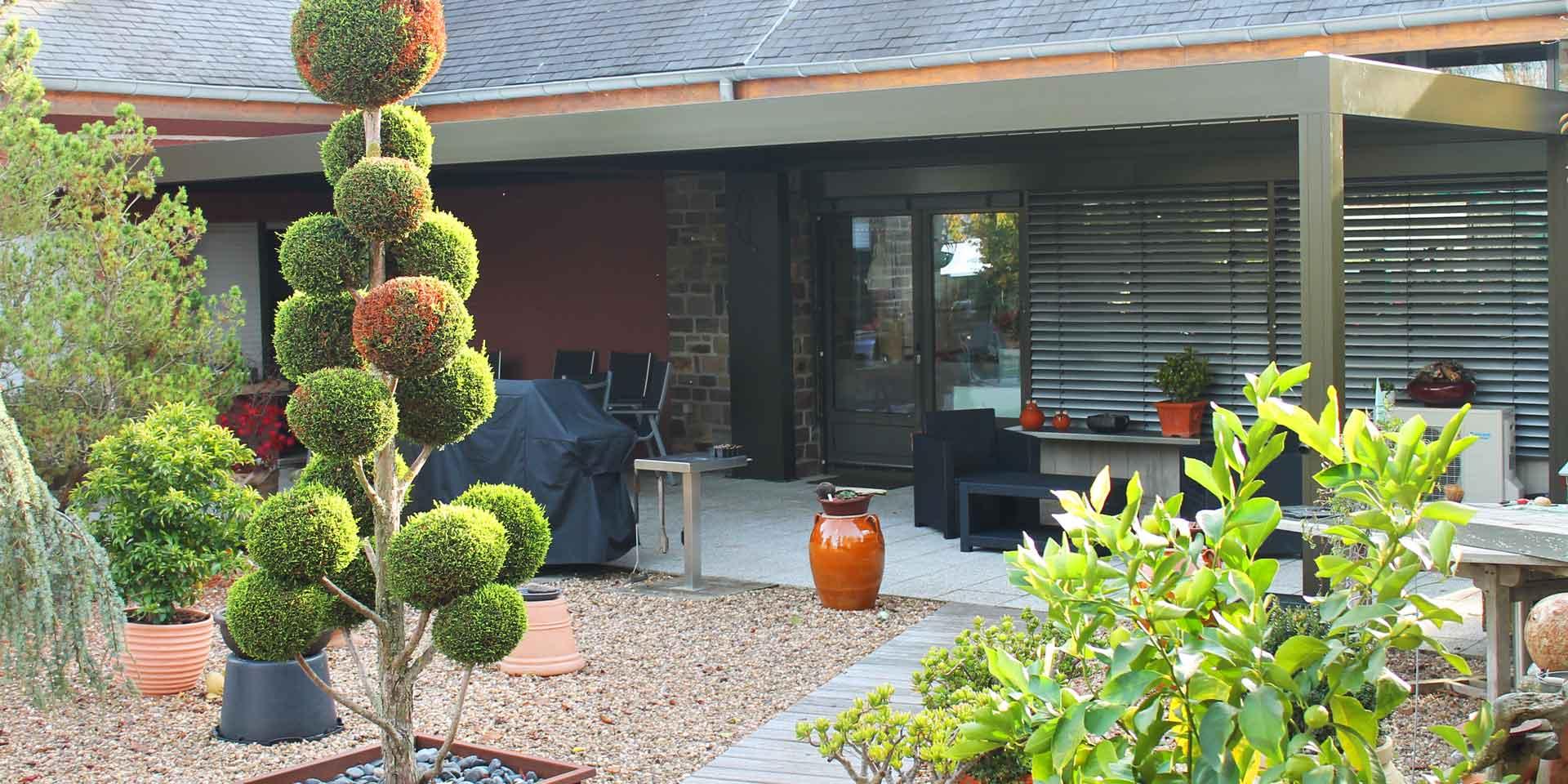 Rotes Einfamilienhaus mit Nahaufnahme der Rückseite des Hauses mit Blick auf ein graues Quadrato mit gekoppelter Aluminium Coplaning geschlossener Terassenüberdachung mit Lamellendach.