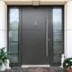 Nahaufnahme des Eingangsbereichs mit Blick auf die graue Coplaning Aluminium Haustür mit Türklopfer.