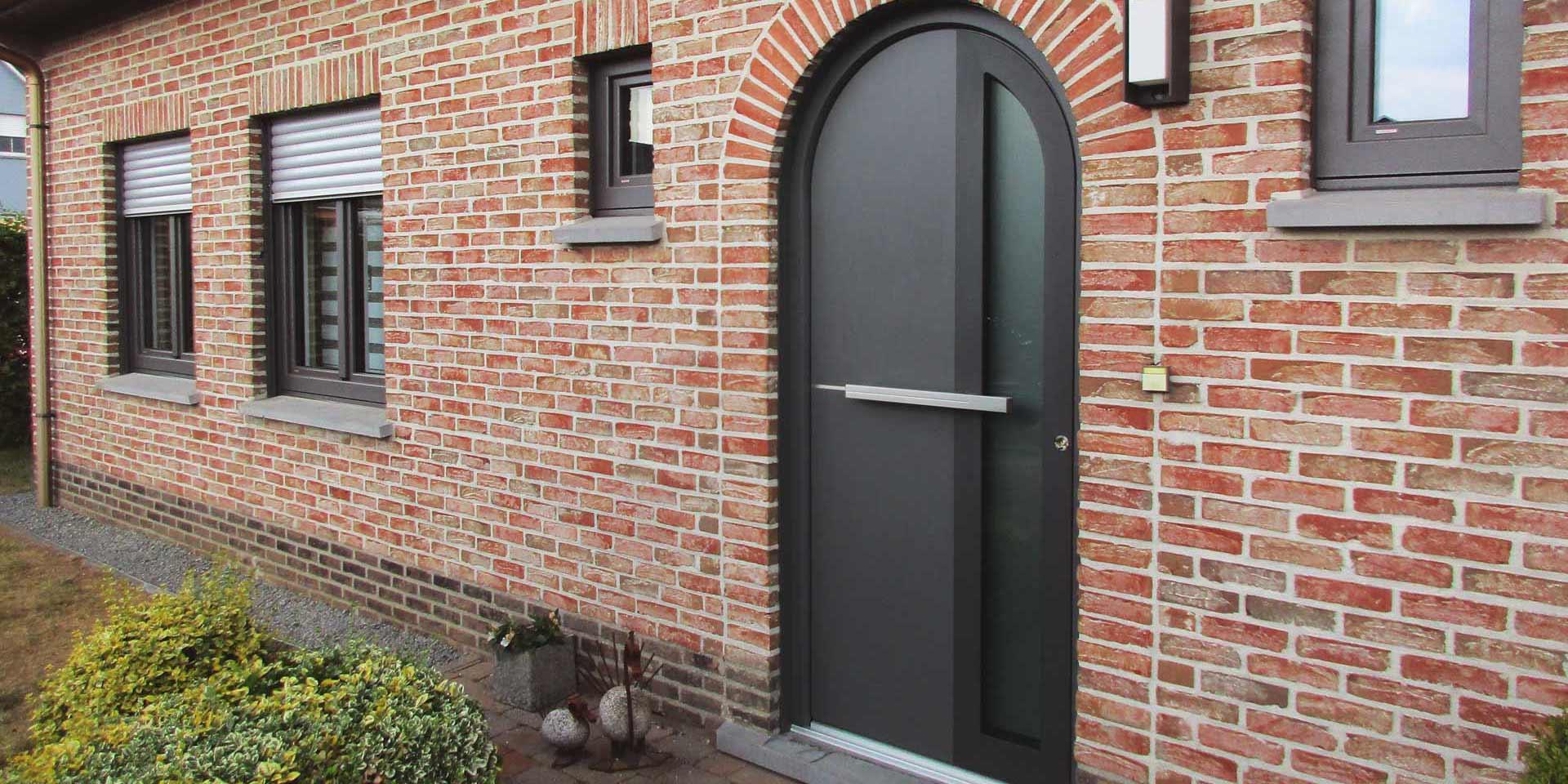 Nahaufnahme des Eingangsbereichs eines Einfamilienhauses mit Steinfassade mit einer modernen grauen Coplaning Haustür.