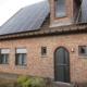 Vorderseite des Einfamilienhauses mit Steinfassade mit moderner grauen Coplaning Haustür.
