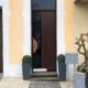 Nahaufnahme auf den Eingangsbereich eines gelben Einfamilienhauses mit Blick auf die neue moderne braune Coplaning Haustür.