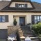 Weißes Einfamilienhaus mit einer modernen grauen Coplaning Haustür und grauen Coplaning Holzfenster mit grauen Klappläden.