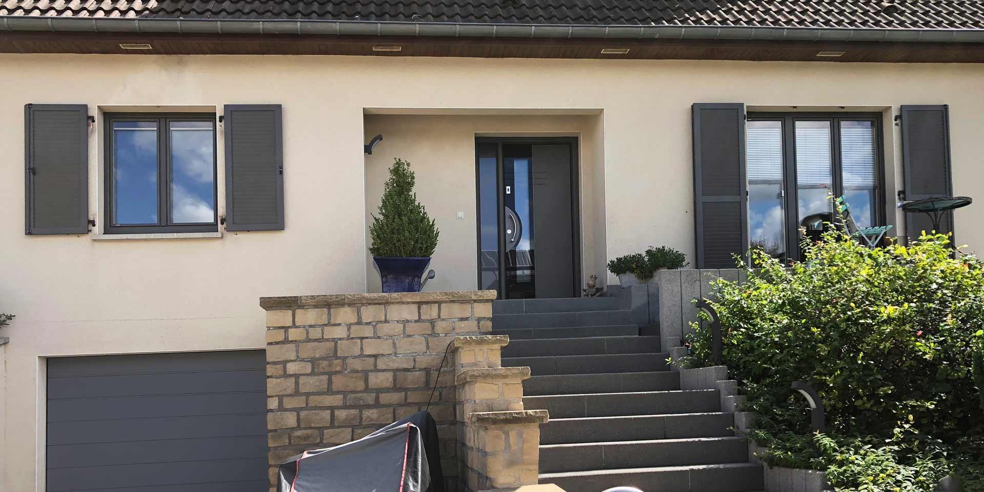 Nahaufnahme auf den Eingangsbereich des weißen Einfamilienhauses mit moderner grauer Coplaning Haustür und grauen Coplaning Holzfenster und Klappläden links und rechts von der Coplaning Haustür.