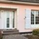 Nahaufnahme vom Eingang des Hauses mit links der neuen weißen Haustür aus Keramik und rechts ein weißes Fenster.