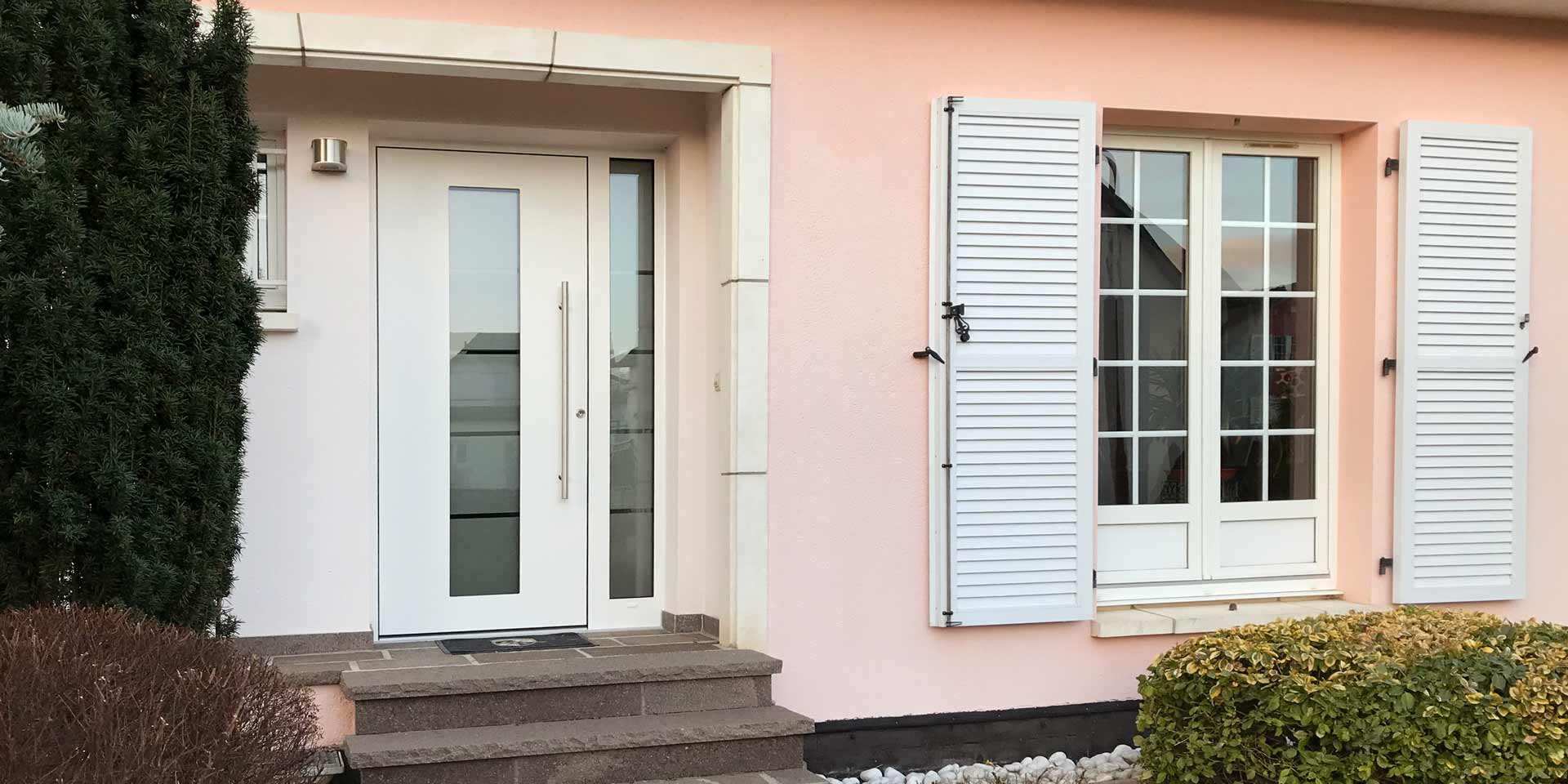 Nahaufnahme vom Eingang des Hauses mit links der neuen weißen Coplaning Haustür aus Keramik und rechts ein weißes Coplaning Holzfenster.