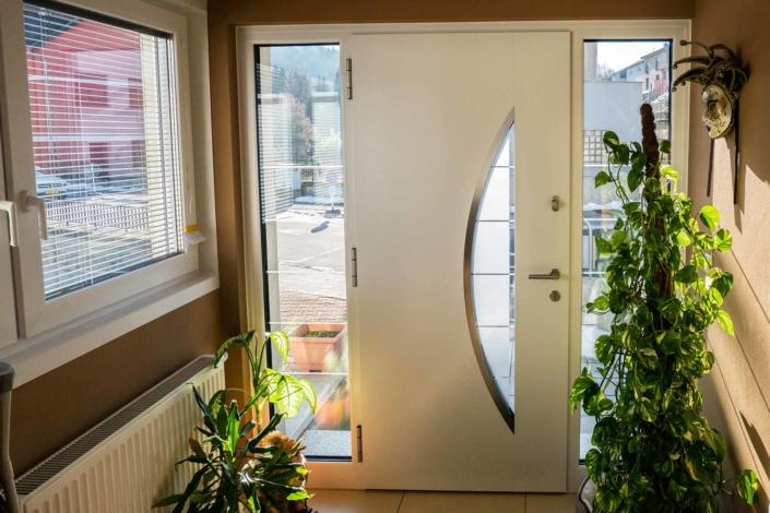 Nahaufnahme von der modernen grau-weißen Aluminium Coplaning Haustür des weißen Einfamilienhauses von innen.